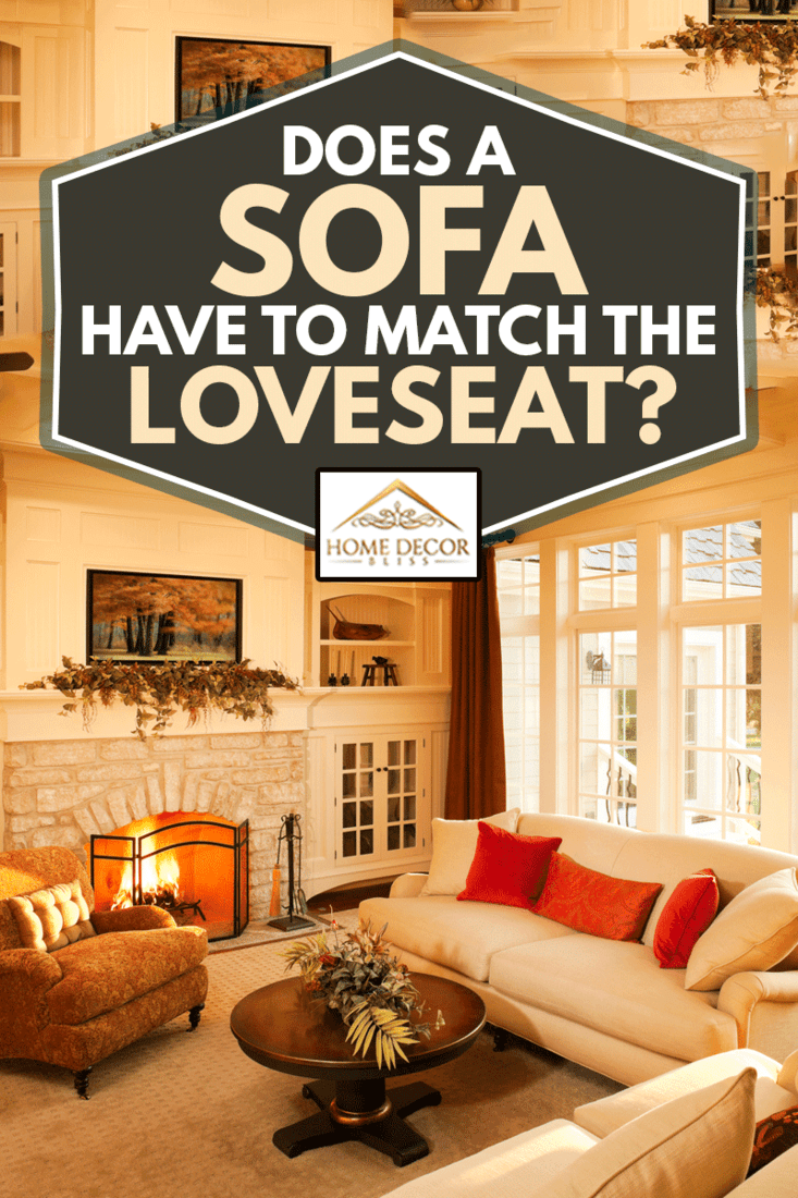 Warm afternoon sunlight pours into an elegant homes living room with a stone fireplace and large windows looking out into the yard with loveseat and sofa, Does A Sofa Have To Match The Loveseat?