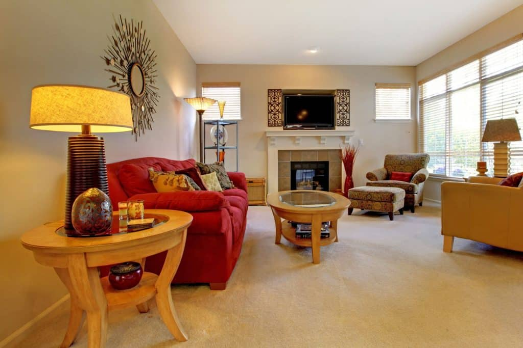 Elegant living room with beige carpeted flooring, red sleeper couch, and a fireplace on the background