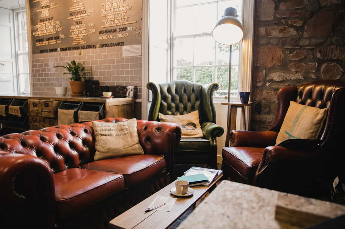 Empty interior of a small cafe, there is a seating area with leather sofas and a wooden table, furniture in earth tones