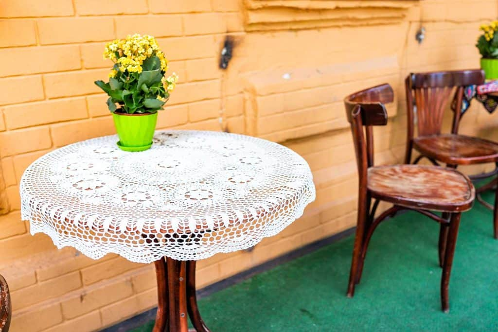 Empty wooden table outside restaurant cafe with chairs on sidewalk street and yellow flowers in flowerpot potted plant setting