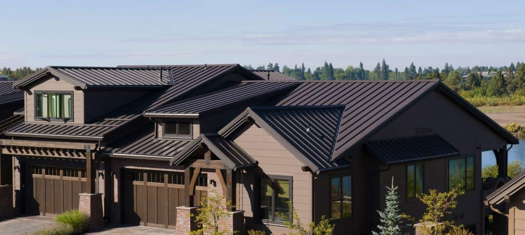 Exterior of a luxurious brown two storey lake house with brown roofing seams paired wit brown wooden paneled sidings