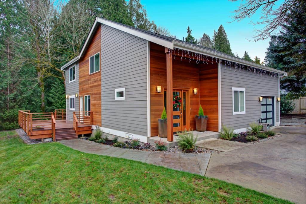 Exterior of a modern rustic home with gray and wooden vinyl sidings