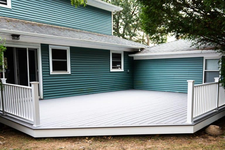 Exterior of a residential home with blue vinyl sidings and a composite deck on the backyard, How To Keep Spiders And Other Bugs Off Vinyl Siding