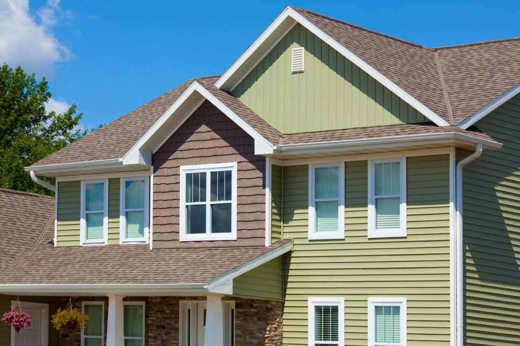 Exterior of a two storey house with brown weathered shingle roofing and green painted vinyl sidings