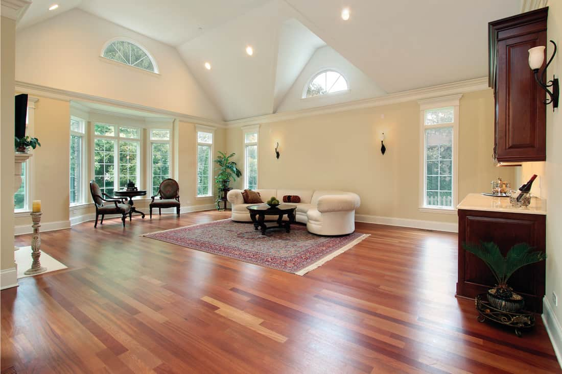 Family room with curved windows and dark laminate flooring