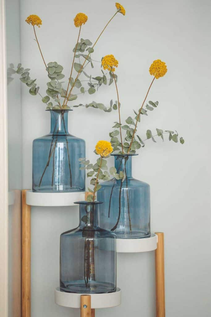Flower arrangement in bottle containers