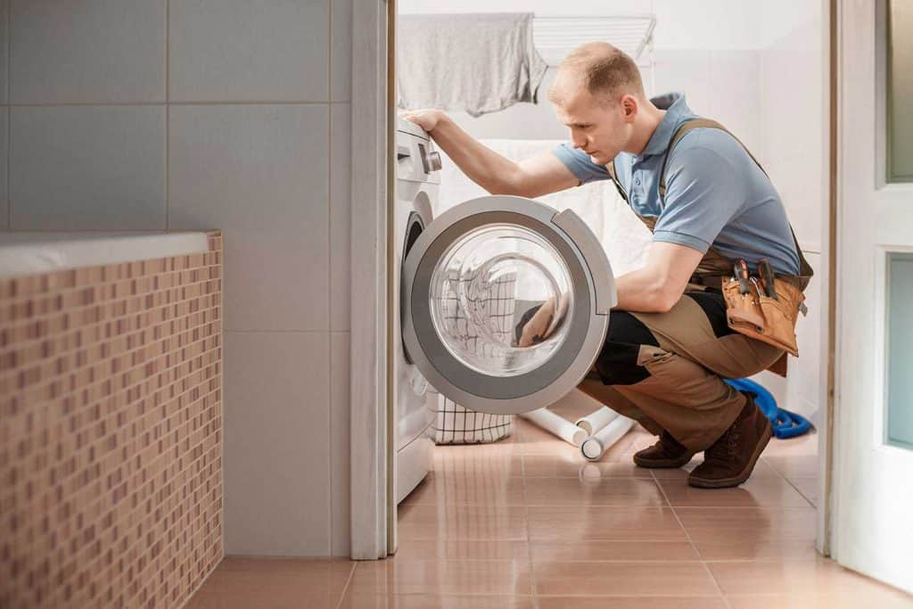 Focused plumber with toolbelt repairing washing machine