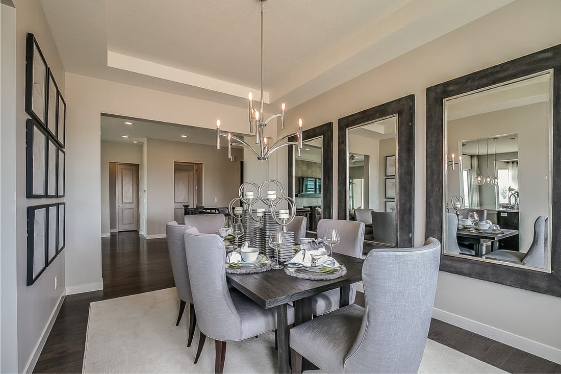 Formal dining room with a thick in group of wall mirrors, candle chandelier, table set for dinner