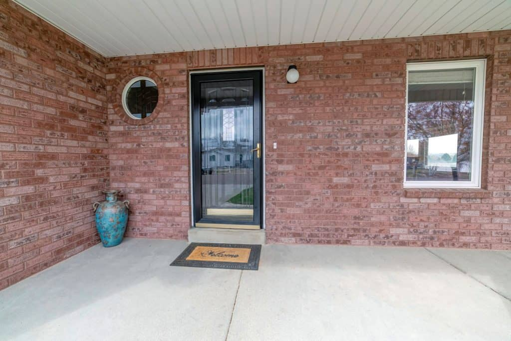 Front porch of a brick house with a glass door and black colored door frames