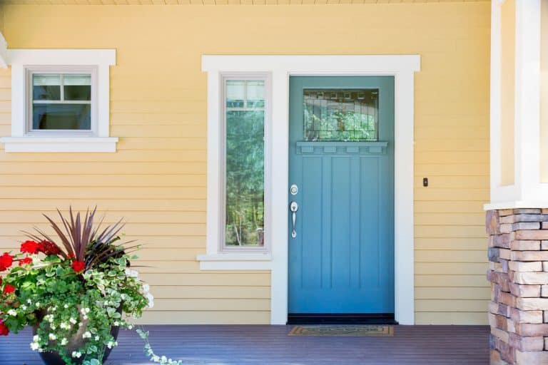 Front-porch-of-a-house-with-a-cream-colored-wooden-siding,-blue-front-door,-and-plants-outside