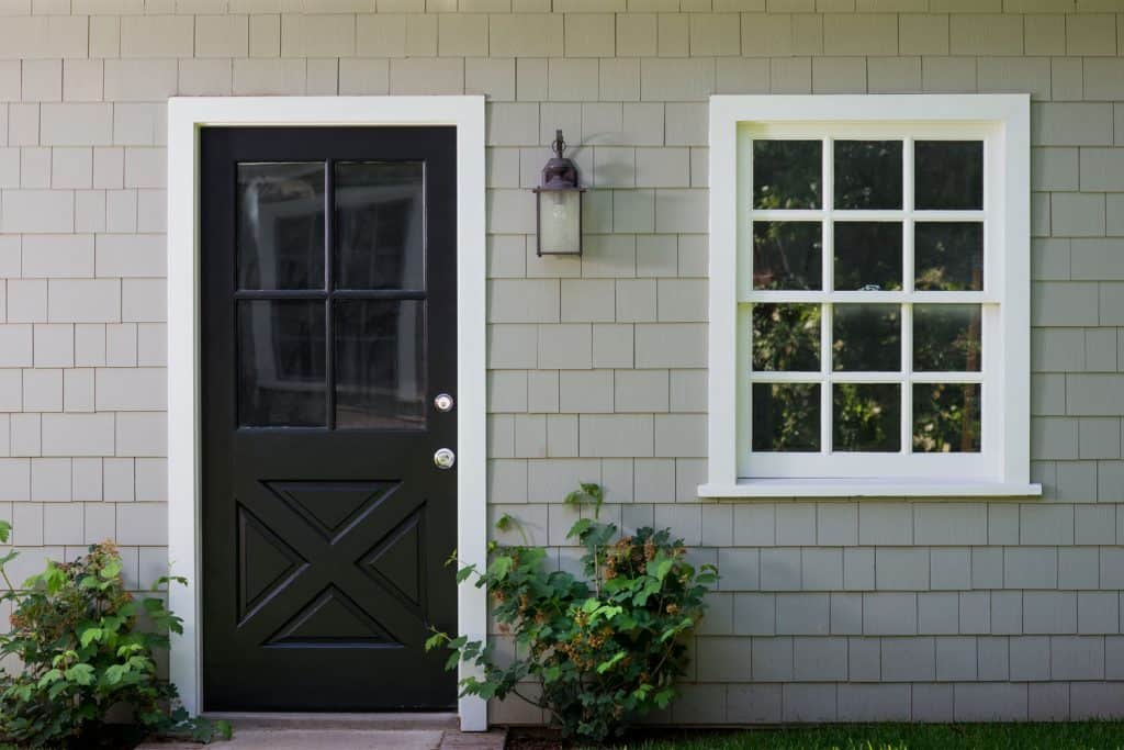 Front porch with shingle roofing, black windowed front door, and a small window on the side