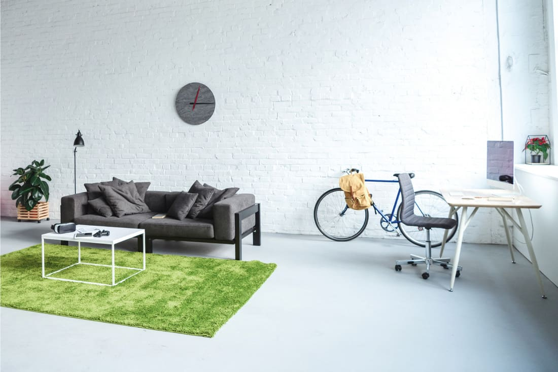 Grass green area rug with light gray flooring, black sofa, bicycle and a work desk