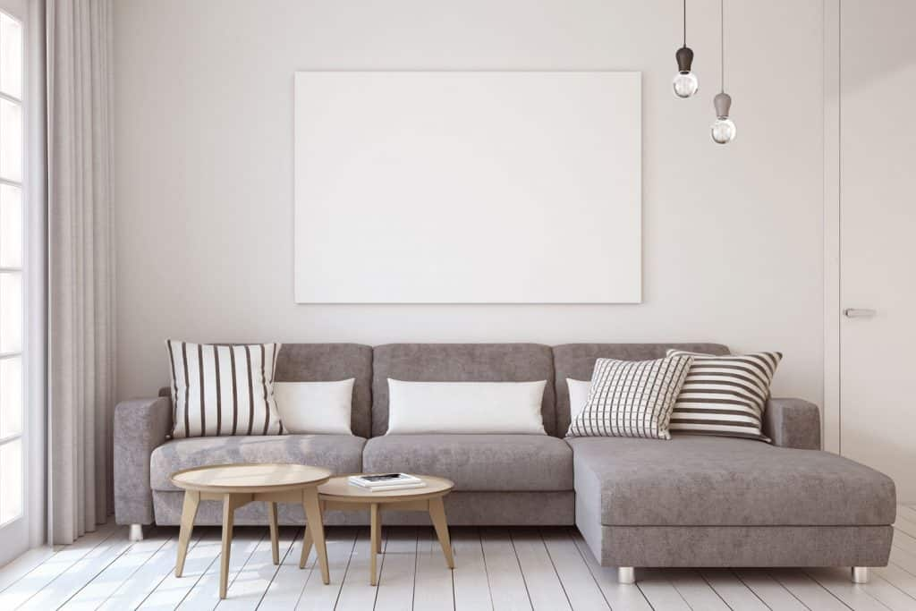 Gray sectional sofa with stripped throw pillows, round coffee tables and dangling lamps