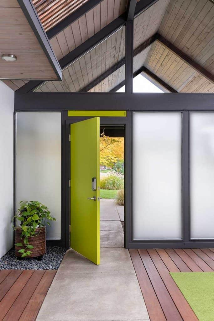 Green front door of a mid-century modern house