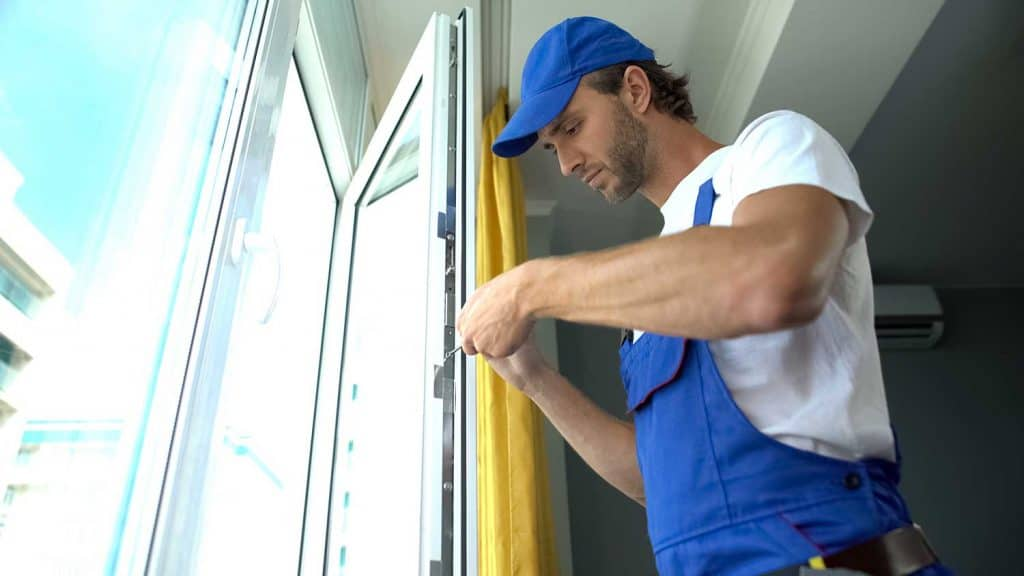 Handyman using screwdriver to fix window, repair and installation services