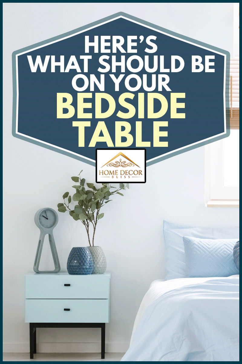 Plant on cabinet bedside table between patterned armchair and blue bed in bedroom interior with lamp, Here's What Should Be On Your Bedside Table