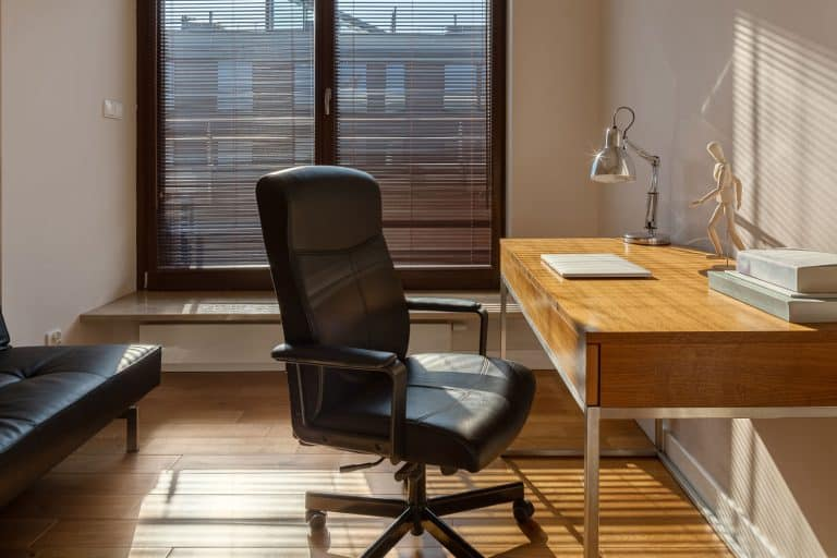 Home office with big window, wooden desk and floor and black office chair and sofa, How to Fix an Office Chair That Leans Back