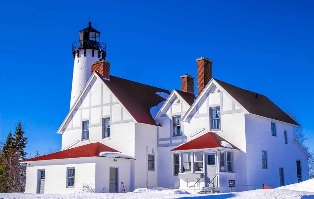 Home with white walls and red roof with lighthouse