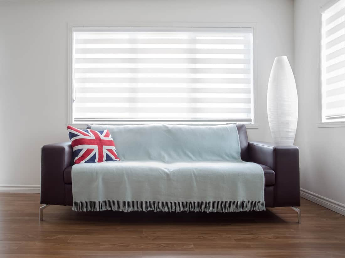 Horizontal image of a modern leather sofa with throw and a Union Jack pillow, in bright living room.