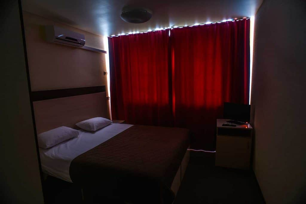 Hotel bedroom with red curtains on window