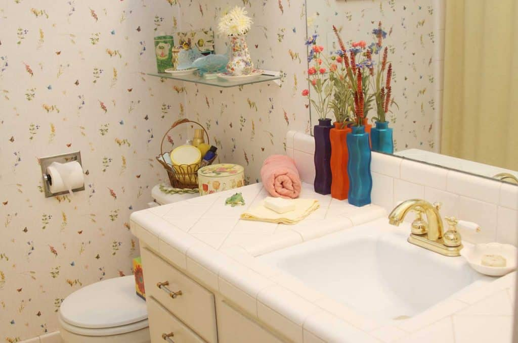 House bathroom with wallpaper and large mirror above sink