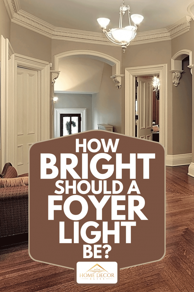 A bright foyer with chandelier and curved staircase, How Bright Should A Foyer Light Be?