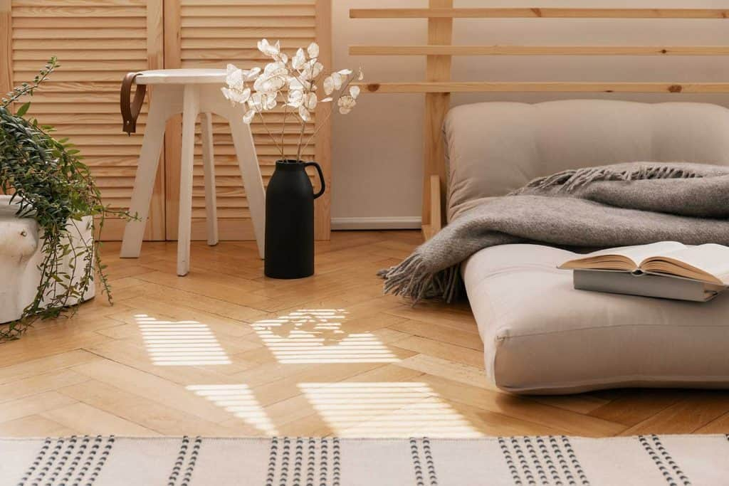 Hygge bedroom with scandinavian futon as a bed next to white flowers in black vase and wooden coffee table