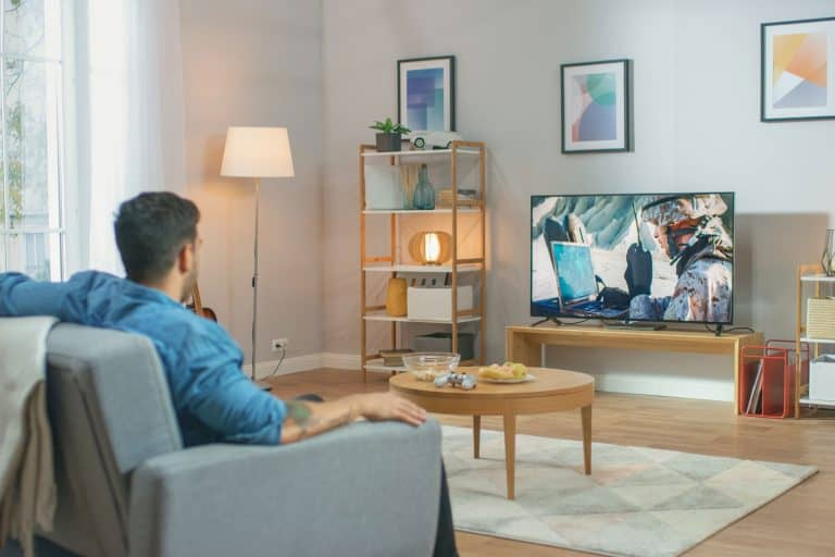 In the Living Room: Guy Relaxing on a Couch Watching War Movie on a TV. Modern Military Warfare Action with War Soldiers Shown on a Television, Can You Put a TV in Front of a Window?