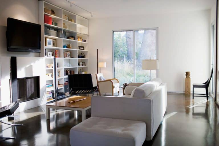 Interior of a contemporary designed living room with walls painted in white, a tall bookshelf, and a white sofa in the center, Where To Put Bookcases In Your Home
