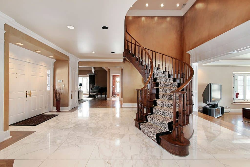 Interior of a huge two story mansion with a gray foyer