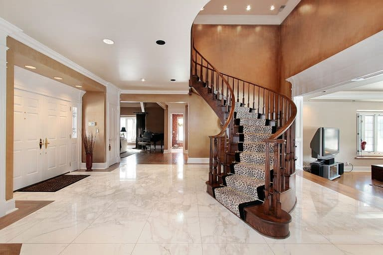 Interior of a huge two story mansion with a gray foyer, spiral wooden handrail staircase and patterned white tiled flooring, Should Foyer And Living Room Be Same Color?