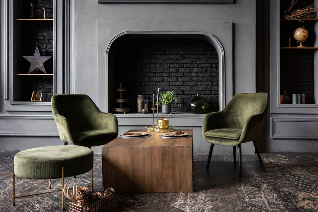Interior of a large living room with modern Victorian themed architecture, gray small chairs, small green ottoman with a wooden coffee table on the center
