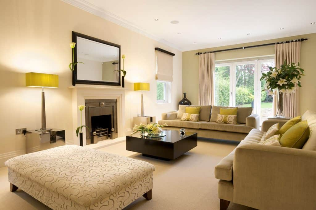 Interior of a luxurious living room with cream painted walls, beige carpet and a fireplace with beige colored fireplace mantel and cream sofas with cream ottoman