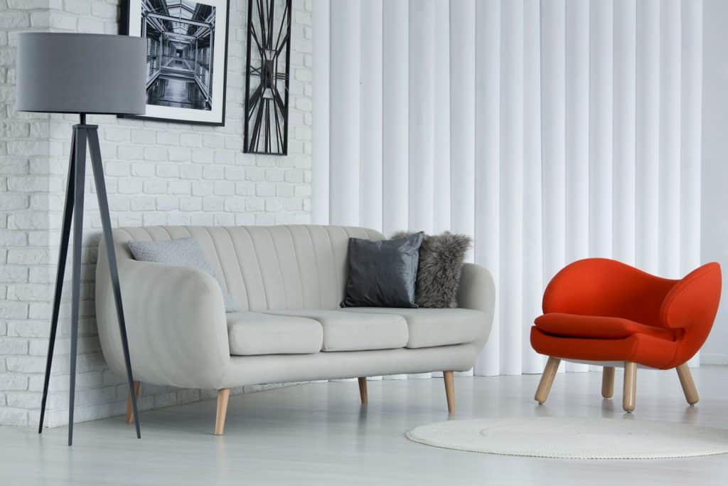 Interior of a modern contemporary living room with a white sofa and gray throw pillows, and a small red chair
