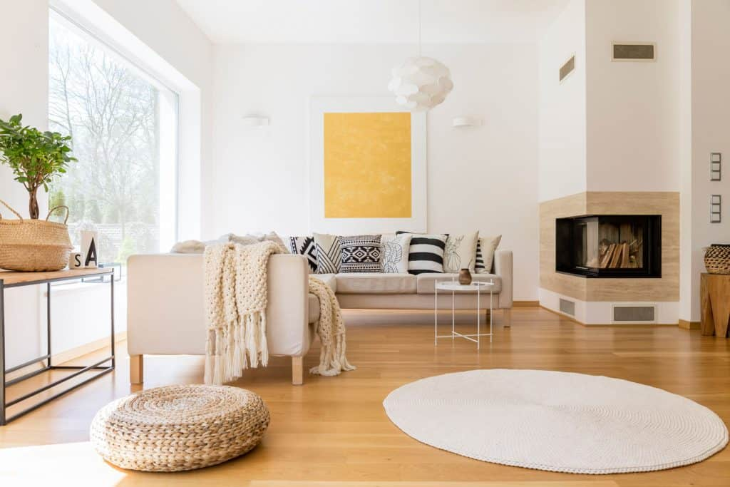 Interior of a modern contemporary living room with laminated flooring, beige sectional sofa, a small ottoman on the side, white painted walls