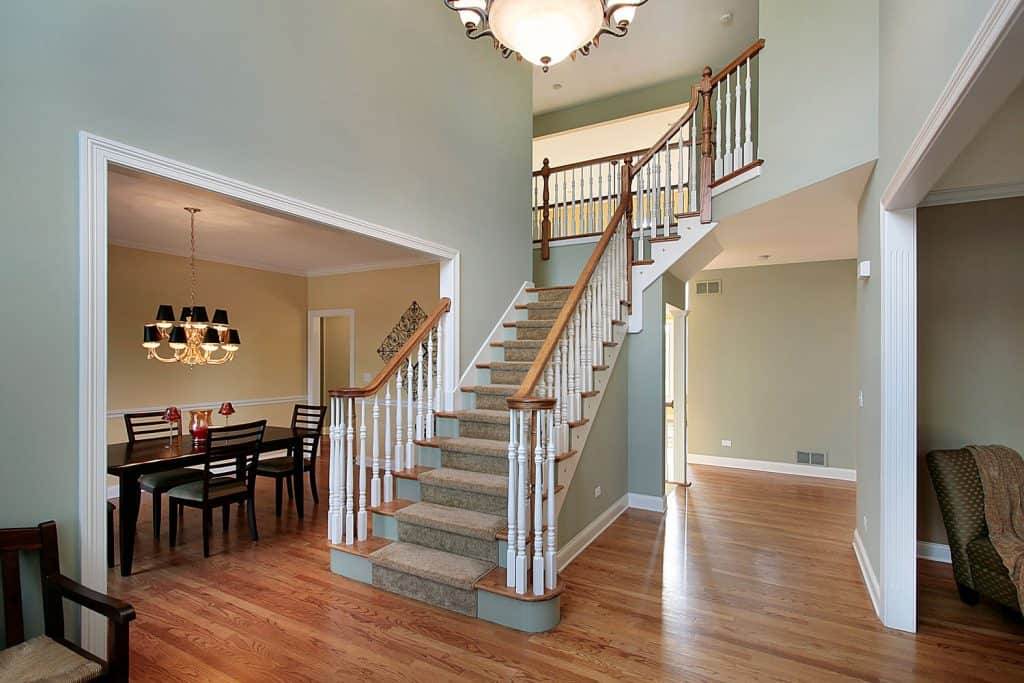 Interior of a modern rustic living room with a grand foyer with white painted banisters and wooden flooring