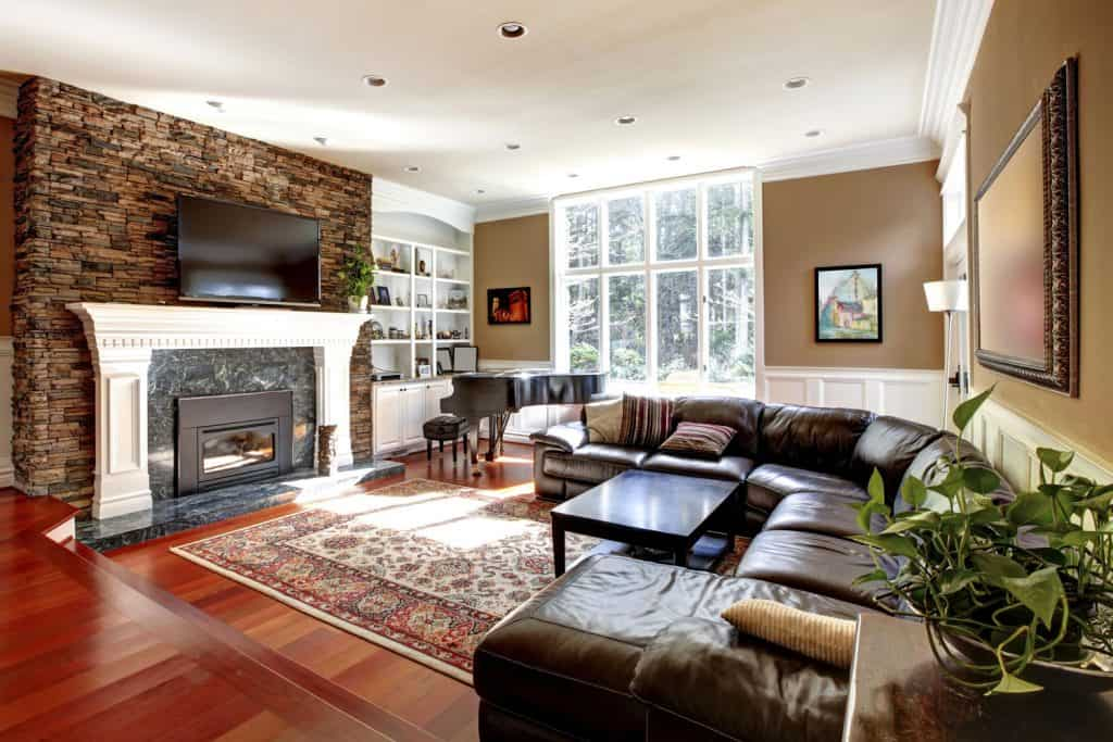 Interior of a modern rustic living room with brown painted walls, hardwood flooring, brown leather sectional sofas, and a white painted fireplace mantel