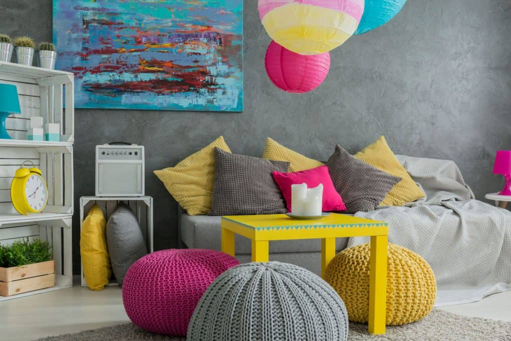 Interior of a retro themed living room with multi-colored throw pillows, yellow coffee table, and multi colored ottomans, and a gray faux wall