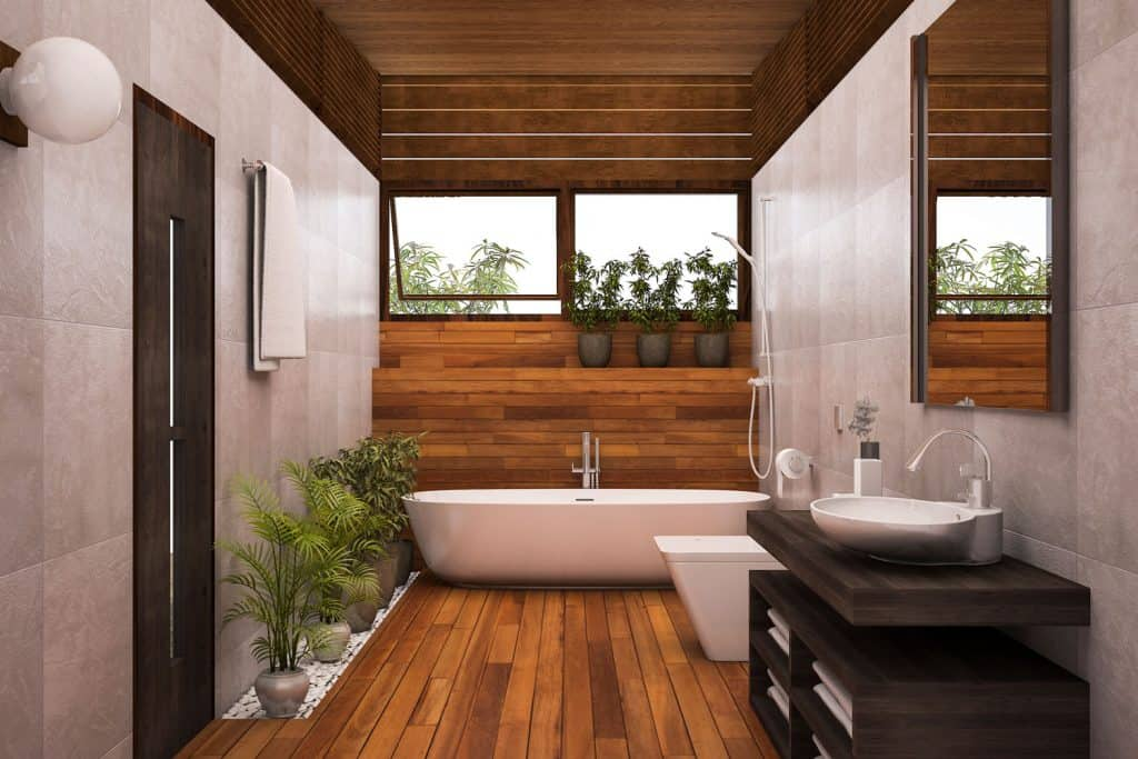 Interior of a rustic contemporary bathroom design matched with wooden flooring, gray walls, and indoor plants on the side