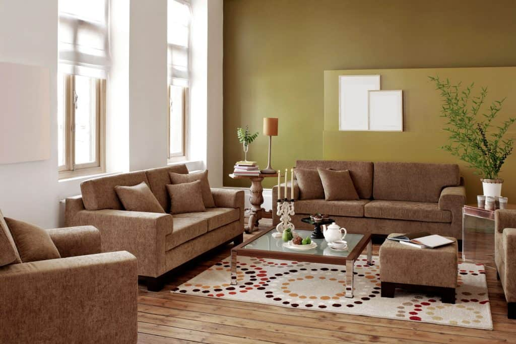 Interior of a rustic themed living room with brown square armed chair sofas, small brown ottoman, and a glass coffee table