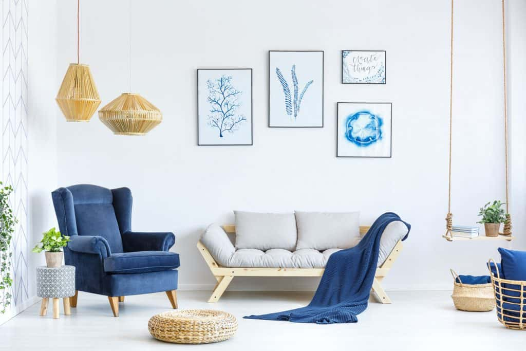 Interior of a simple minimalist inspired living room with a blue accent chair, light gray sofa, and dangling golden lamps
