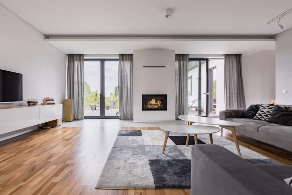 Interiorof a spacious contemporary living room with wooden flooring, gray sofas, white coffee table, and white painted walls with a fireplace on the middle