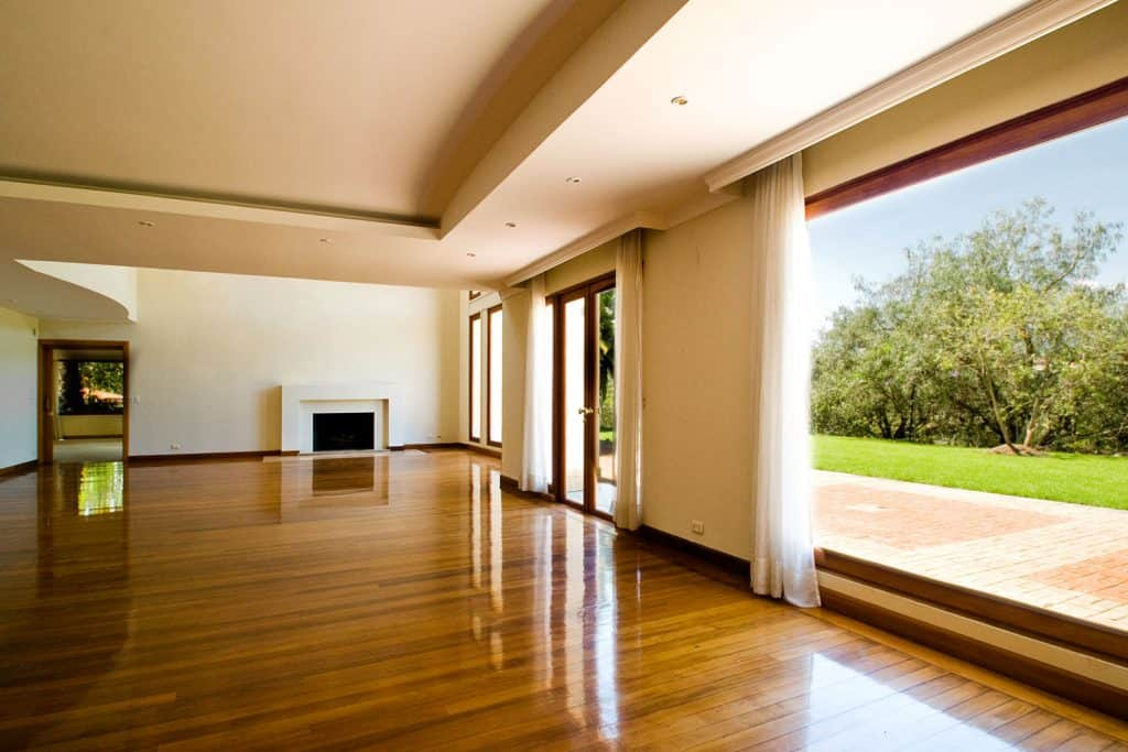 Interior of a spacious living room with polished hardwood flooring and a huge picture window with white curtains