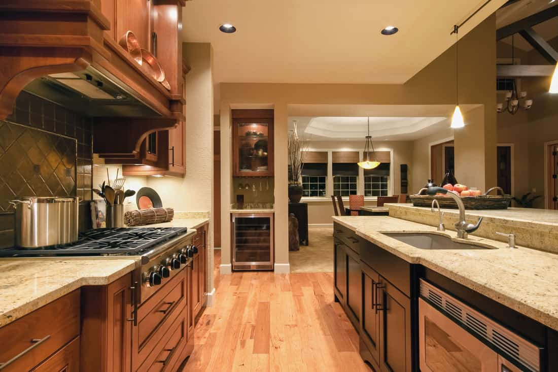Interior of a vintage themed kitchen with marble countertops, wooden flooring, and oak cabinetry