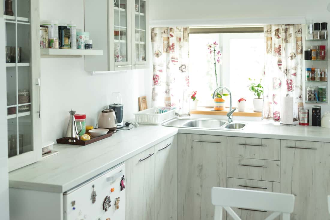 Interior of modern white wooden kitchen with white floral curtains above the sink