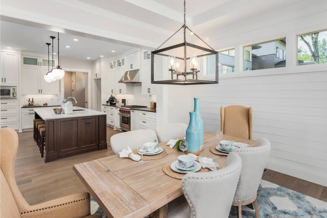 Kitchen with island, sink, cabinets, wooden dining table and hardwood floors