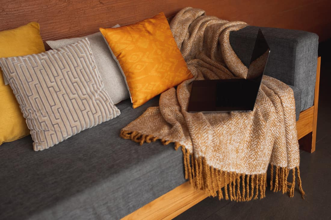 Laptop on gray sofa with yellow pillows and wool blanket on it. Blogger freelancer home workspace office. Modern colourful interior design concept.