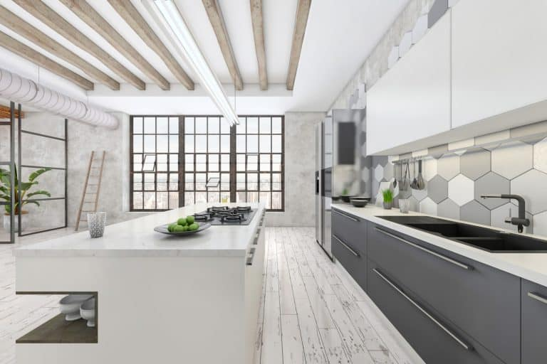 Large modern kitchen interior with white kitchen counter. Grey tiled wall, parquet, sink, window and concrete wall in the background