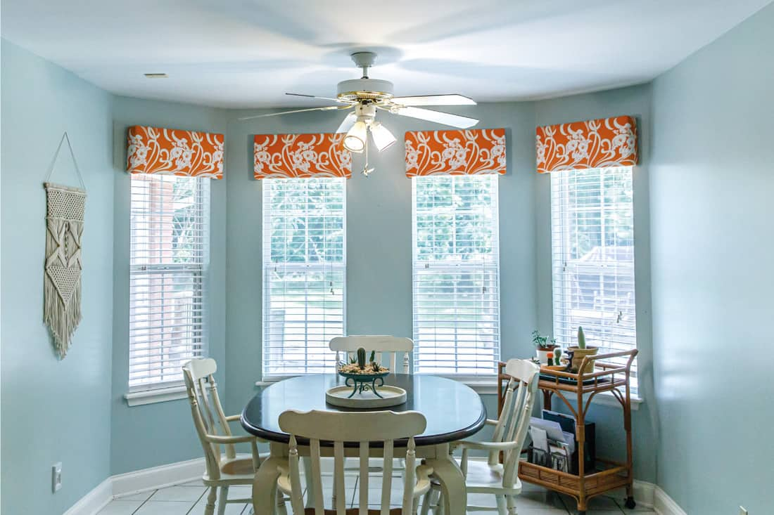 Light Blue Eat-In Dining Room next to the kitchen with a tile floor, table and chairs, vibrant box valances and blinds