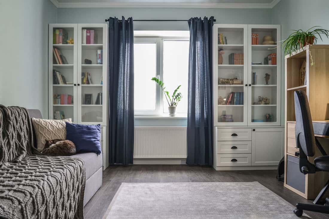Light cozy teen room with white bookcases, grey sofa and blue walls and long curtains, How To Make Curtains Longer [3 Ways]